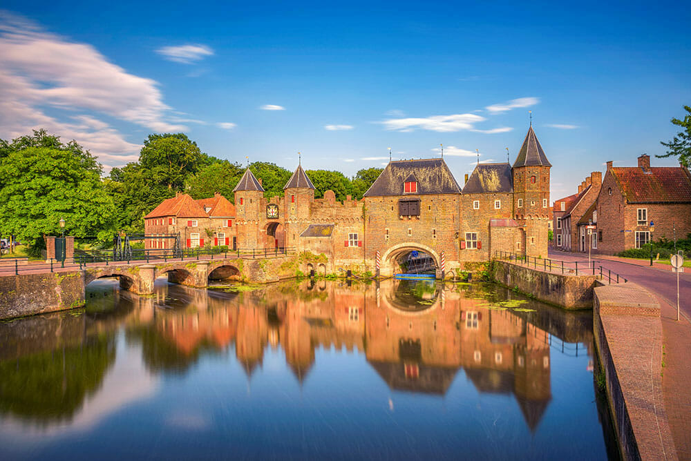 Red brick fortified medieval gate reflected on water