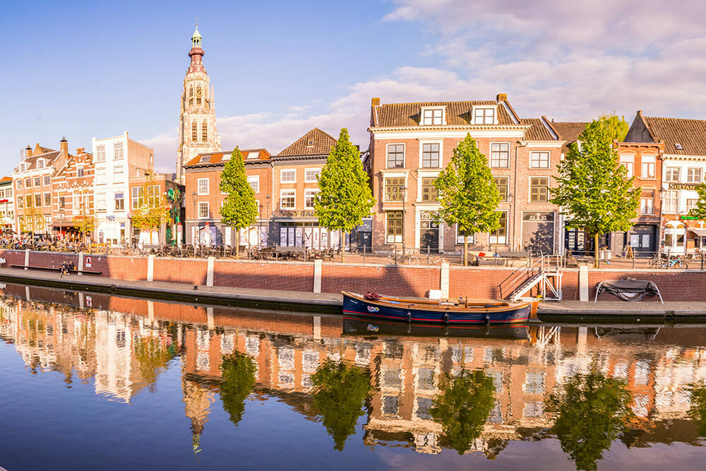 Two and three storey houses and a tall church tower along a canal