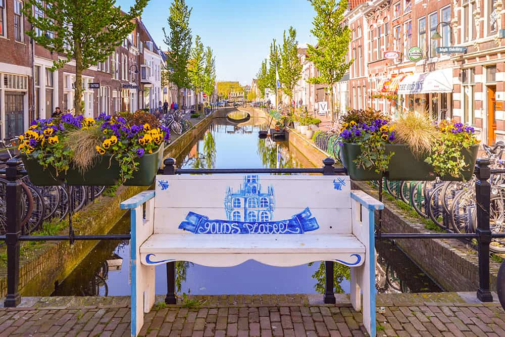 Wooden bench painted white and blue with a canal and typical Dutch houses behind